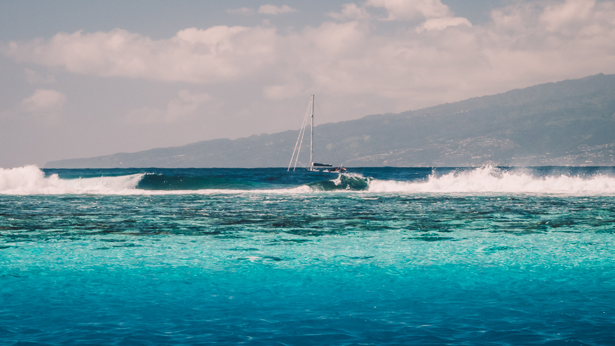 sailboat crashing through the waves outside of the barrier reef in moorea french polynesia