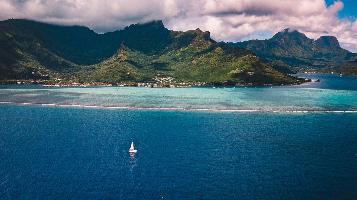 sailing vessel curiosity sailing along moorea, french polynesia