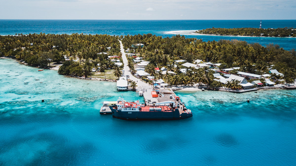 drone view of rangiroa atoll in tuamotu and a supply ship at harbor