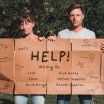 nikki and jason wynn holding up natural disaster relief sign about how to help with hurricane, fire, cyclone relief