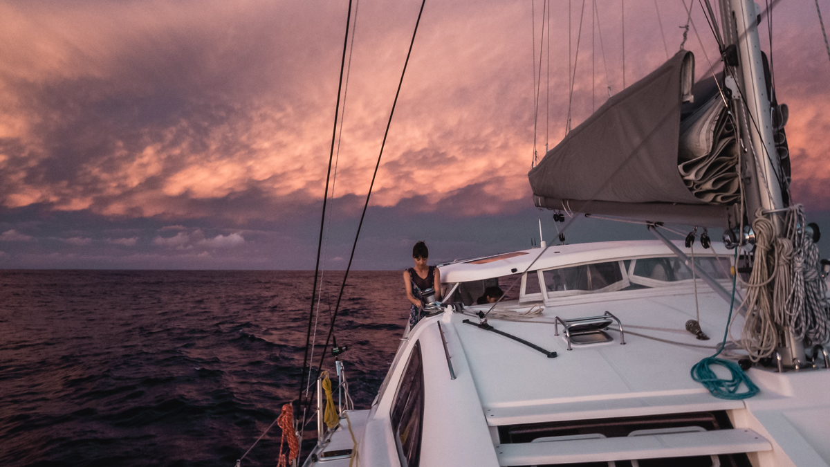 nikki wynn working the sails aboard sailing vessel curiosity at sunset in the south pacific
