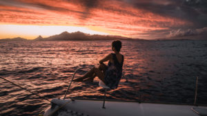 nikki wynn on the bow of sailing vessel curiosity at sea in the south pacific