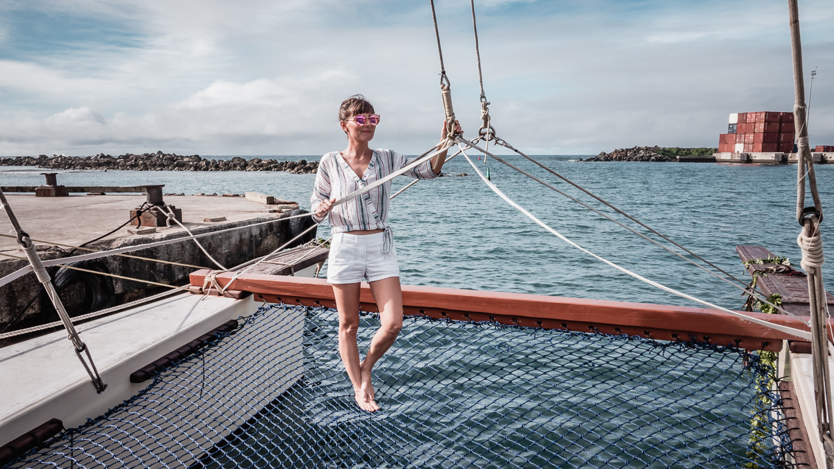 Nikki Wynn on the bow of traditional polynesian sailing vessel in cook islands south pacific