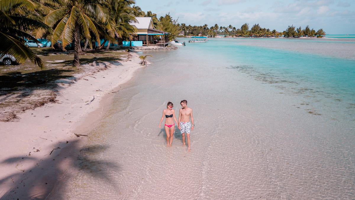 nikki and jason wynn walking along beach in Aitutaki
