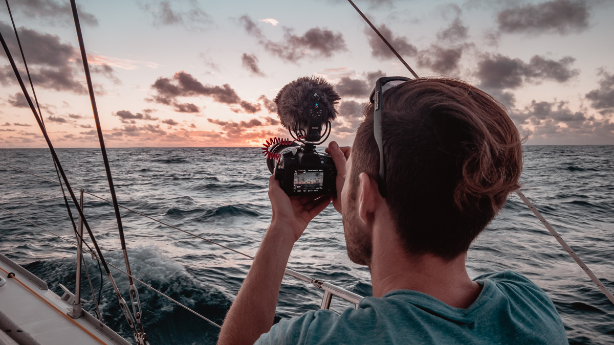 jason wynn capturing photos and video of a sunset at sea while sailing aboard catamaran curiosity