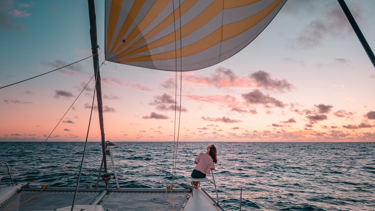 nikki wynn enjoying a beautiful downwind sunset sail aboard sailing catamaran curiosity