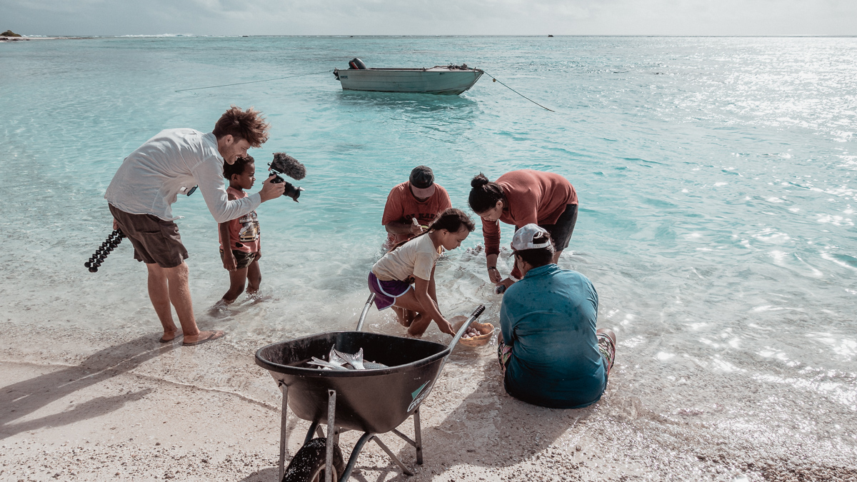 jason wynn capturing natives cleaning fish on palmerston island, cook islands