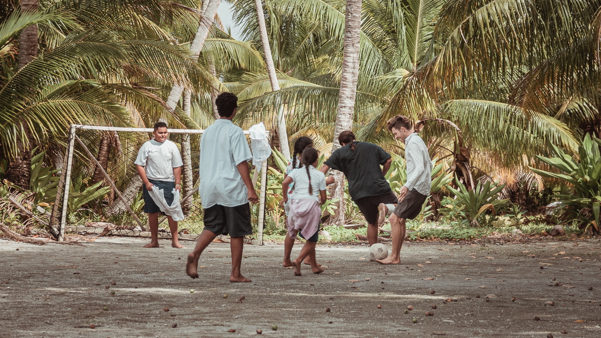 kids playing soccer in palmerston island, cook islands