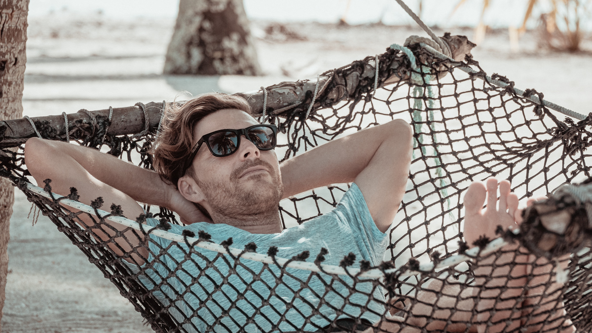 jason wynn relaxing in hammock on palmerston island, cook islands