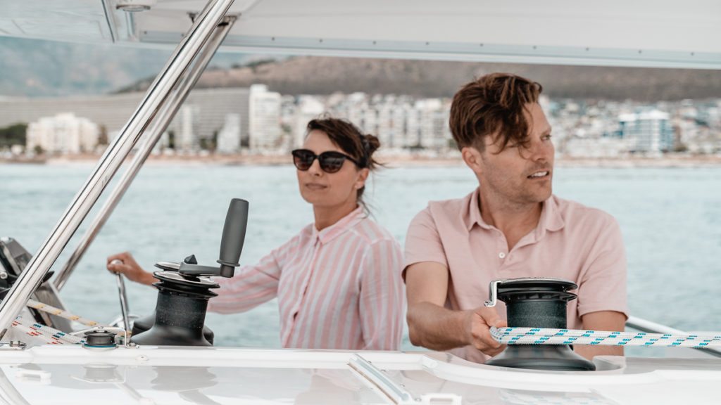 jason and nikki wynn at the helm of a leopard catamaran in south africa