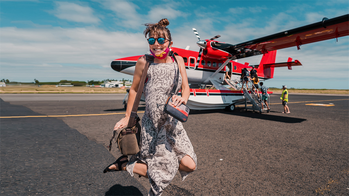 nikki wynn jumping for joy as she heads into a seaplane for a tour over fiji islands