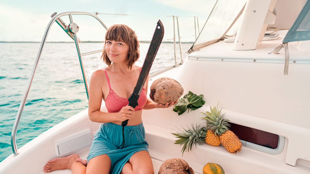 nikki wynn, self reliant sailor cracking coconuts aboard curiosity