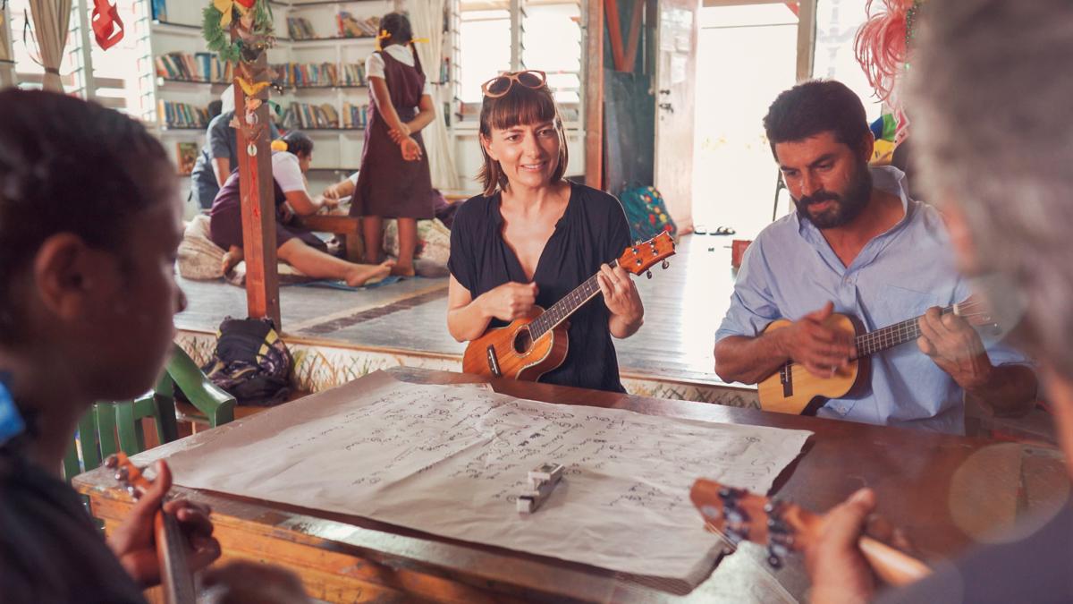 nikki wynn playing ukulele in vava'u library with island kids